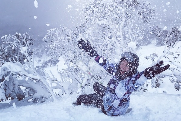 A woman throws snow in Thredbo