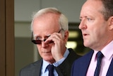 An older man in a suit and sunglasses walks out a building entrance with another man in a suit and pink shirt.