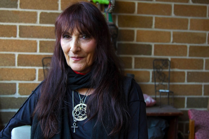 Coven leader Leonora Jackson sitting in front of brick wall.