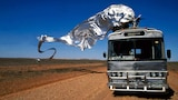 A still from original Priscilla, Queen of the Desert film, with iconic silver wings flying behind a drag queen standing on a bus