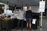 A farmer and worker stand in front of their stall at the farmers' markets.