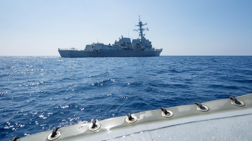 The American guided-missile destroyer USS Dewey is seen in the distance as it transits the South China Sea, May 2017.