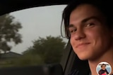A teenage boy smiles at the camera while sitting in the driver's seat of a car.