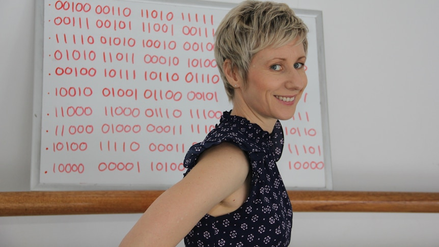 A smiling woman with short blonde hair stands in front of a whiteboard covered with hundreds of binary digits.