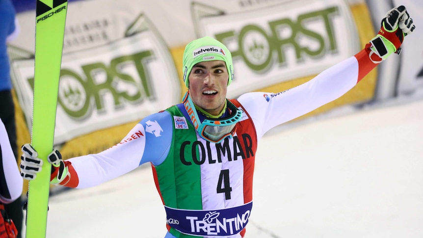 A smiling skier raises his fist in salute to the crowd while holding a ski in his other hand.