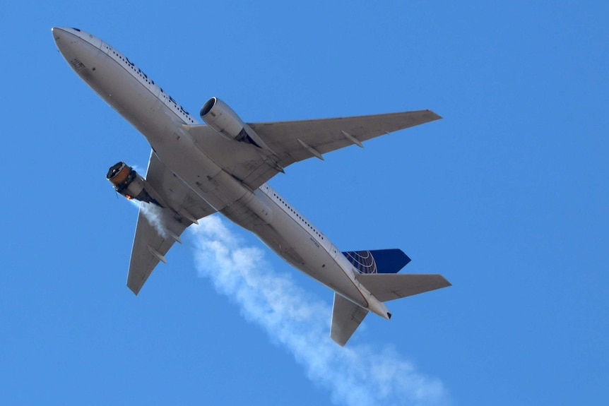 A silver passenger jet blows smoke from its left-hand engine as it flies beneath a blue sky.
