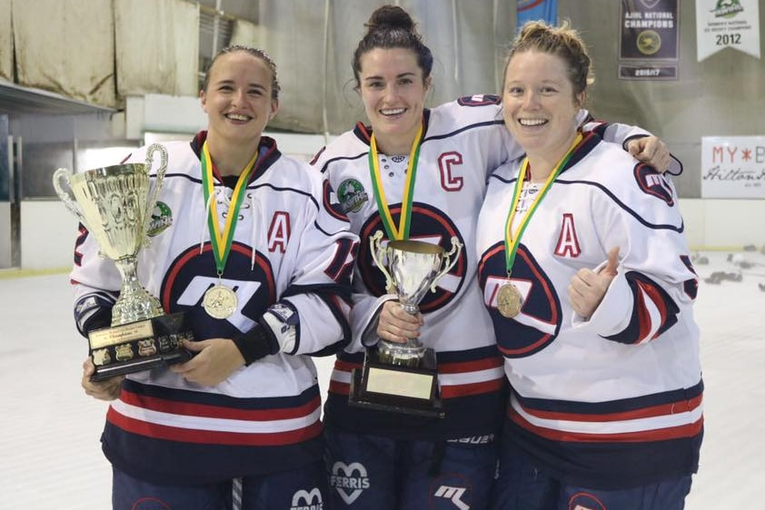 Georgia Moore and Christina Julien smile standing with one of their teammates after winning the Women's Ice Hockey League.
