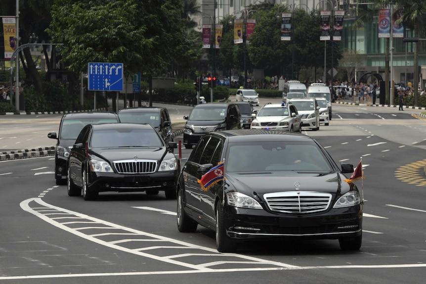 The North Korean motorcade of black sedans and vans travels along Singapore's Orchard Road.