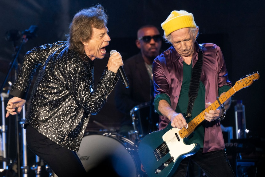 Rolling Stones lead singer Mick Jagger shouts into the microphone, with Keith Richards playing guitar and Steve Jordan on drums.