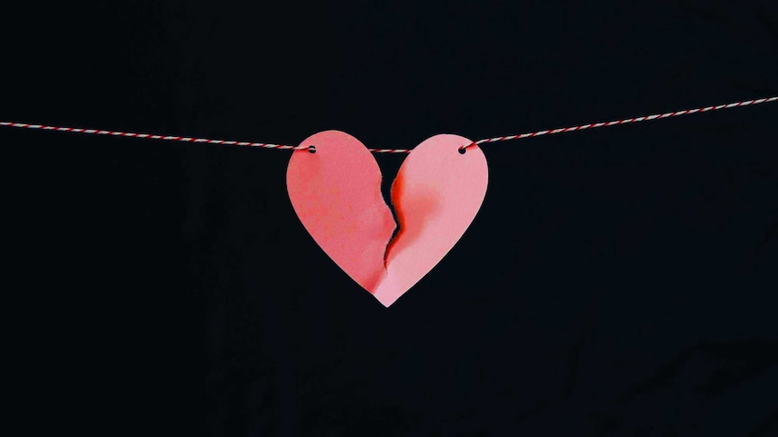 A paper heart hanging on a string is ripped in half to depict how to survive an affair.