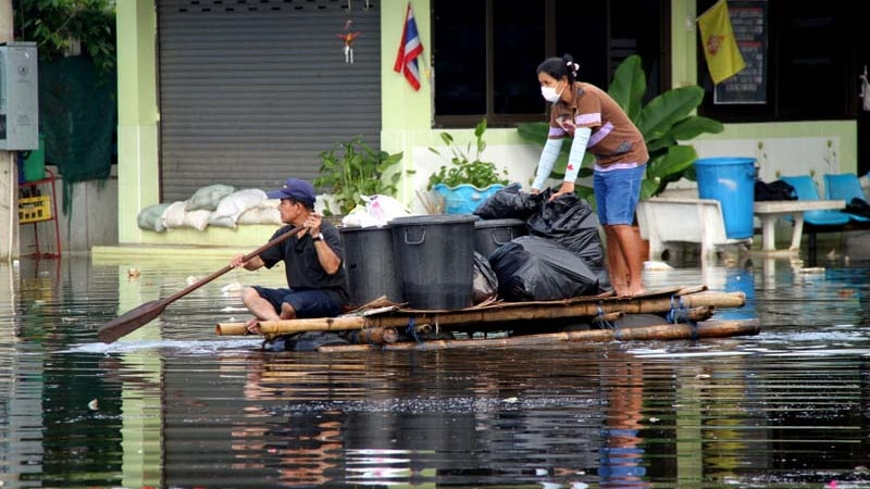 Two people paddle a raft through a flooded street in Bangkok on October 18, 2011.