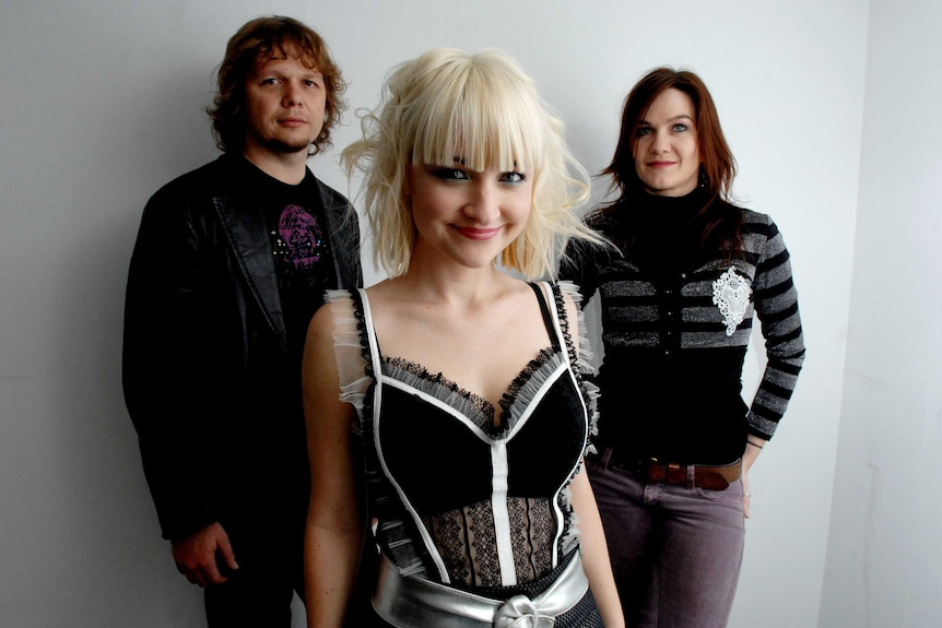 A band photo consisting of three people: A man with shaggy hair, a woman with brown hair and a woman with blonde hair and fringe