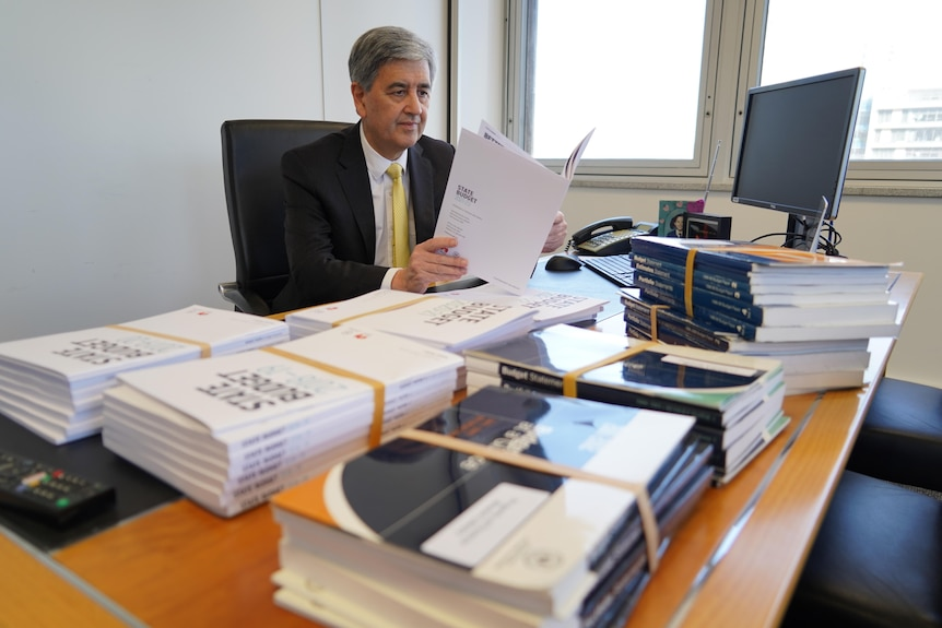 A man sitting at a desk with large documents on it and a computer