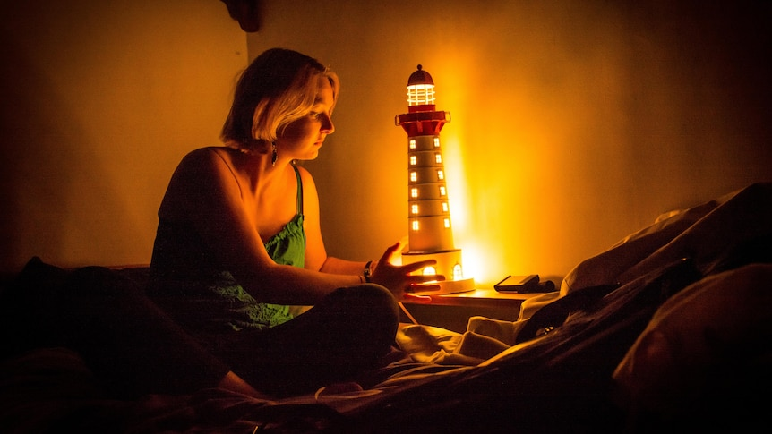 Young woman sitting on bed in the dark holding a night light, in story about managing being scared of the dark.