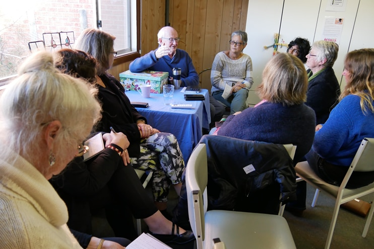 a room of women and one man sit in a circle talking to each other and writing on notepads