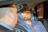 A man wearing forensic coveralls in a car