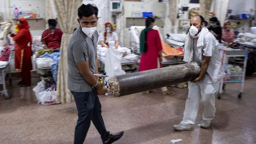 Two men wearing face masks carry an oxygen tank through a busy hospital ward.