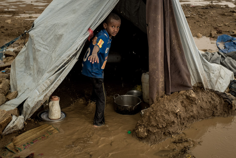 A child inside a tent, which has flooded in the rain.