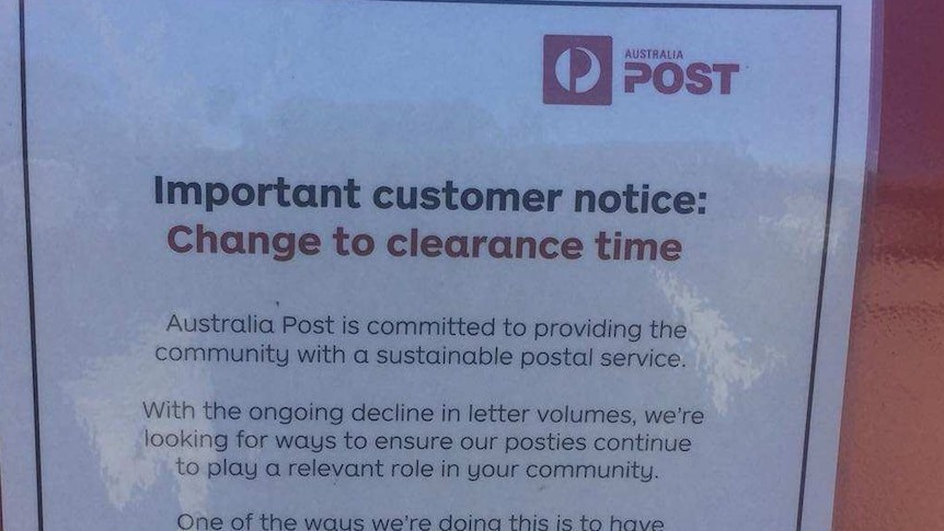 A notice on a post box announces a change to clearing times.