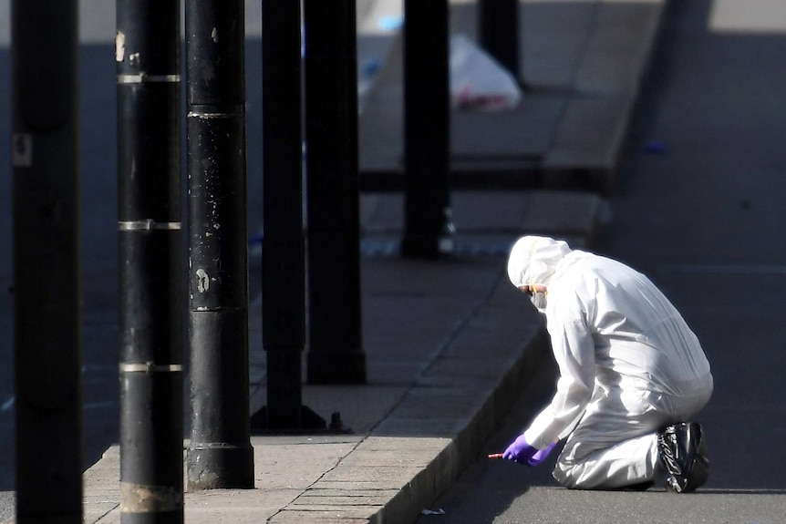 A police forensics investigator wearing a white disposable suit works on London Bridge after the attack.
