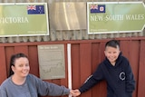 woman standing holding her arm out to a little boy and above them the signs which say Victoria and New South Wales