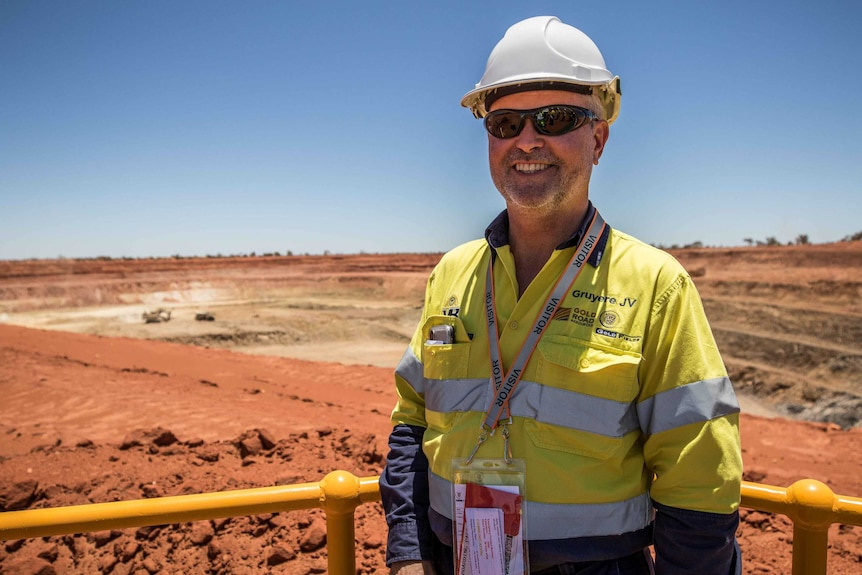 Miner in front of open mine pit