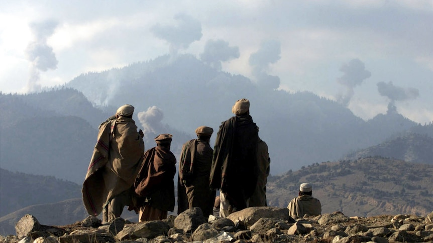 A group of people dressed in black thawb look at mountains with smoke rising in the distance.
