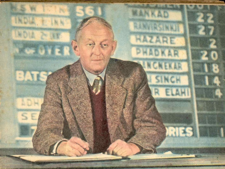 A man sits at a desk in front of an old cricket scoreboard