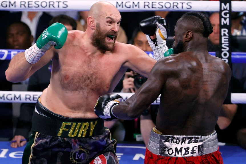 Tyson Fury opens his mouth as he punches Deontay Wilder
