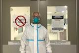 A nurse wears full PPE at work