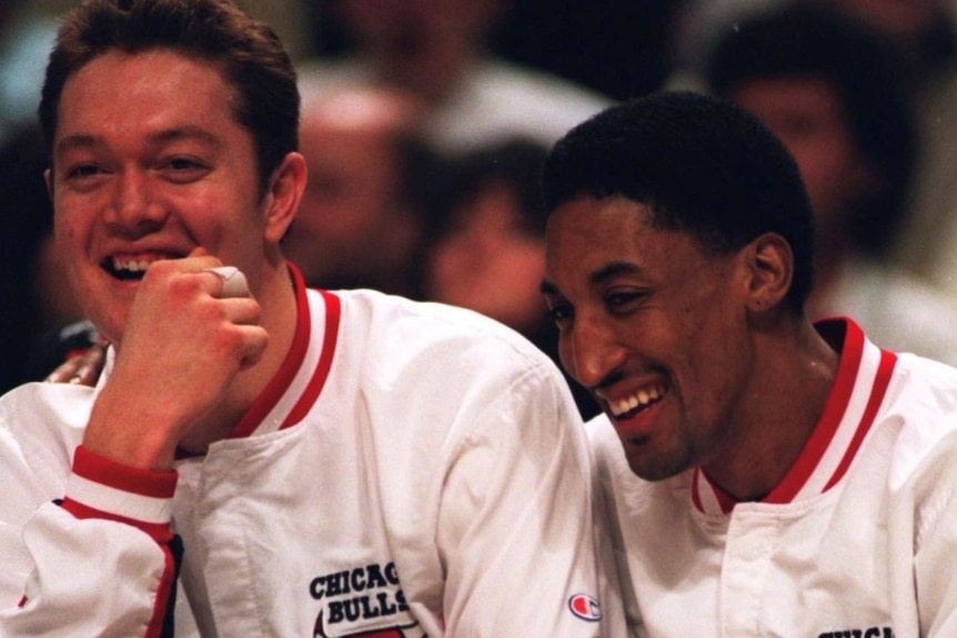 Chicago Bulls players Luc Longley and Scottie Pippen smile wide sitting courtside and wearing tracksuits