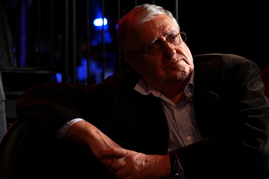 Portrait of a 79-year-old man sitting in a dark theatre on seat