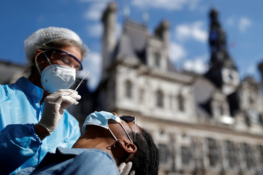A health worker in PPE holds a swab above a man's face