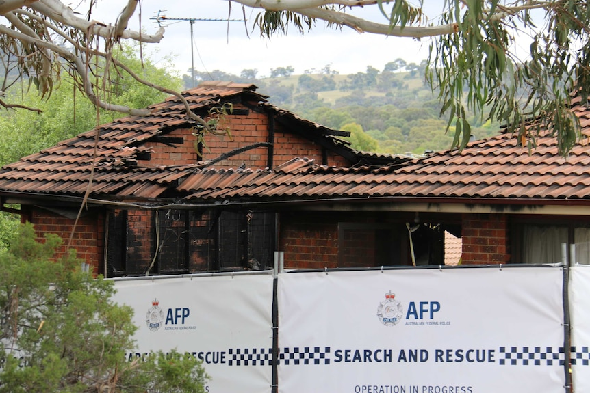 A police barrier in front of a burnt-out house.