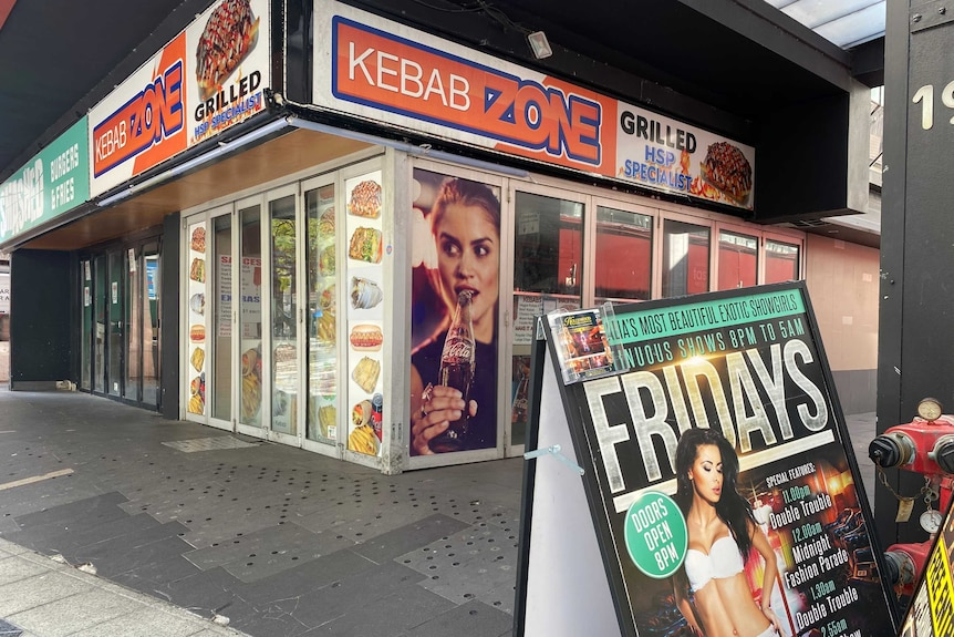 A picture of a closed Kebab shop called Kebab Zone with a billboard for a strip club in the foreground