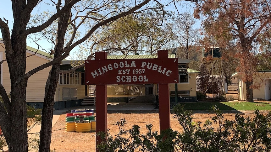 A sign saying Mingoola Public School Est 1957, under a tree in front of primary school buildings and a water tank