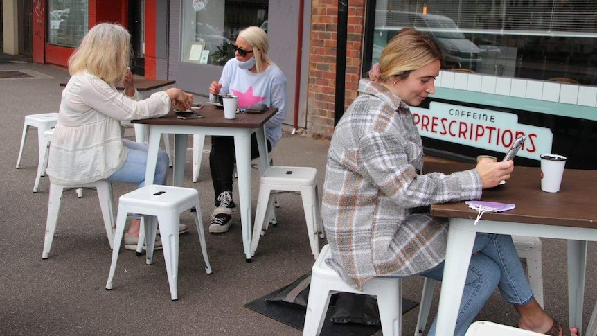 Three women sit at two different tables on a footpath outside a cafe, drinking coffee.