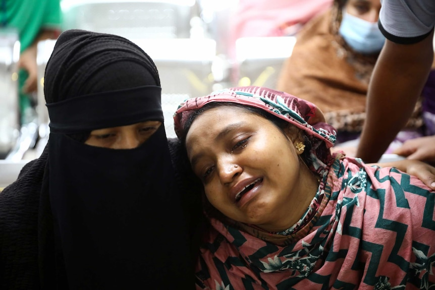 A crying woman leans her head on the shoulder of a woman wearing an Islamic head scarf.