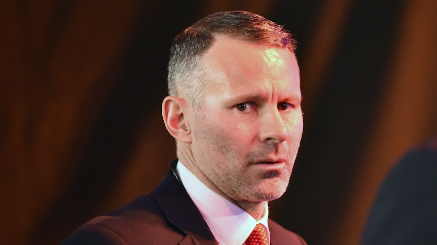 A football manager in a suit looks at the camera.