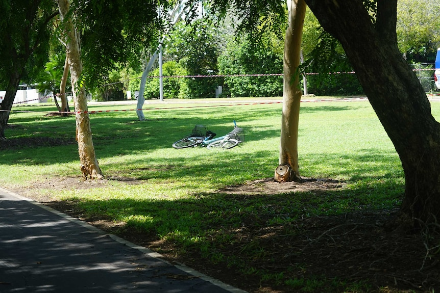 A bike is on its side, surrounded by police tape in a leafy area.