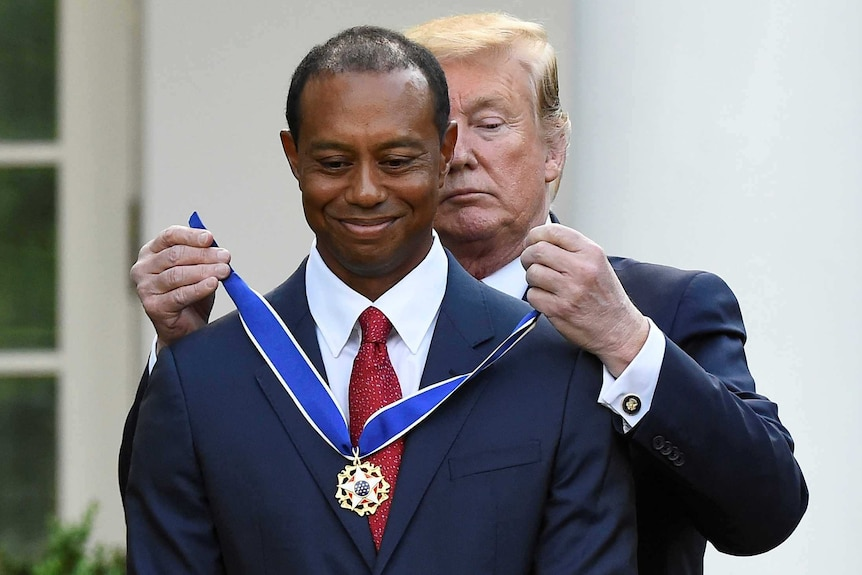 Donald Trump stands behind Tiger Woods as he fastens a medal around his neck
