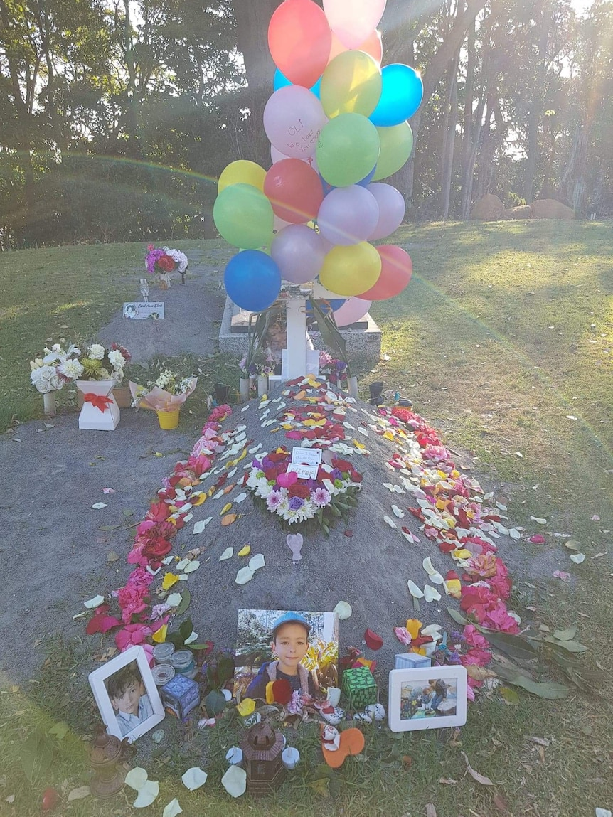 A child's grave with a column of balloons and a ring of flowers, fronted by a photo of a young boy.