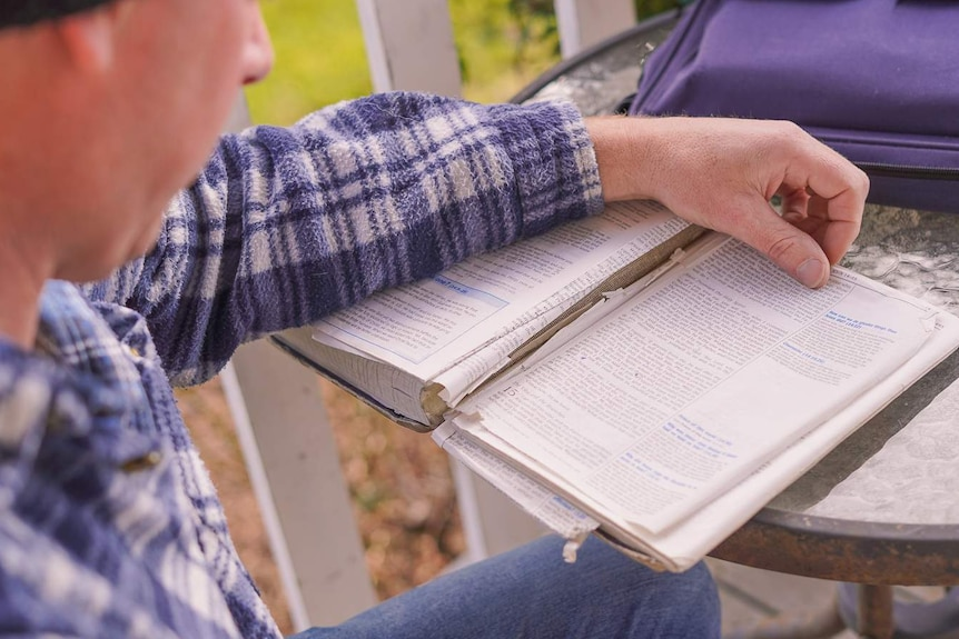 A man in a flannel shirt and beanie sitting at a table turns the page of a bible.