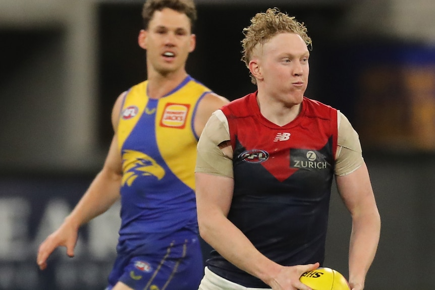 A Melbourne AFL midfielder looks down the field as he shapes to kick the ball during a match.