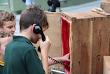 A boy holding the earpiece to an old bakelite phone
