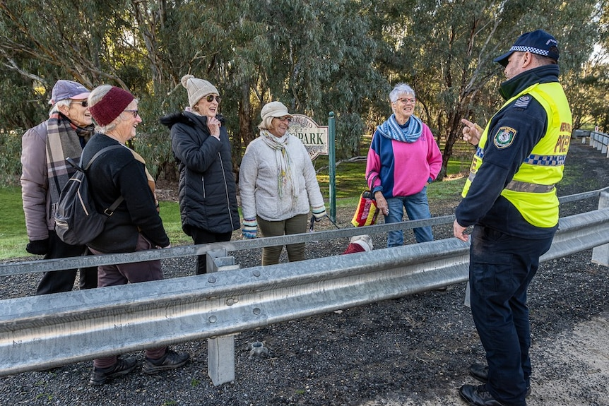 Several elderly women smile and laugh while speaking with a NSW police officer at a bridge checkpoint.