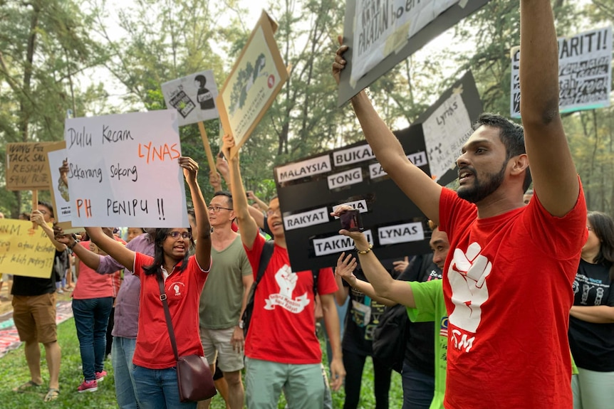A group of Malaysians hold up protest signs.