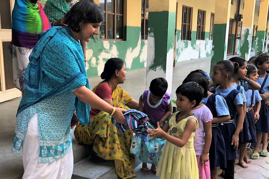 Children lining up to receive a brightly coloured dress from their teacher.