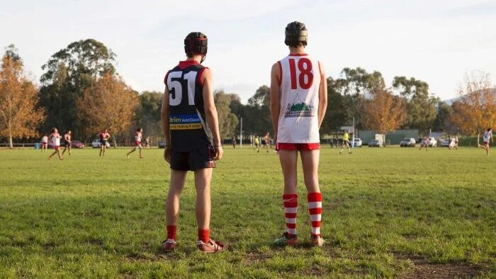 Two junior footballers stand side by side and watch the action during a game.