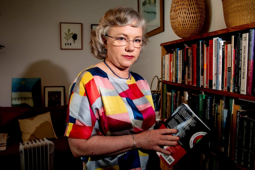 A woman with glasses near a bookcase.